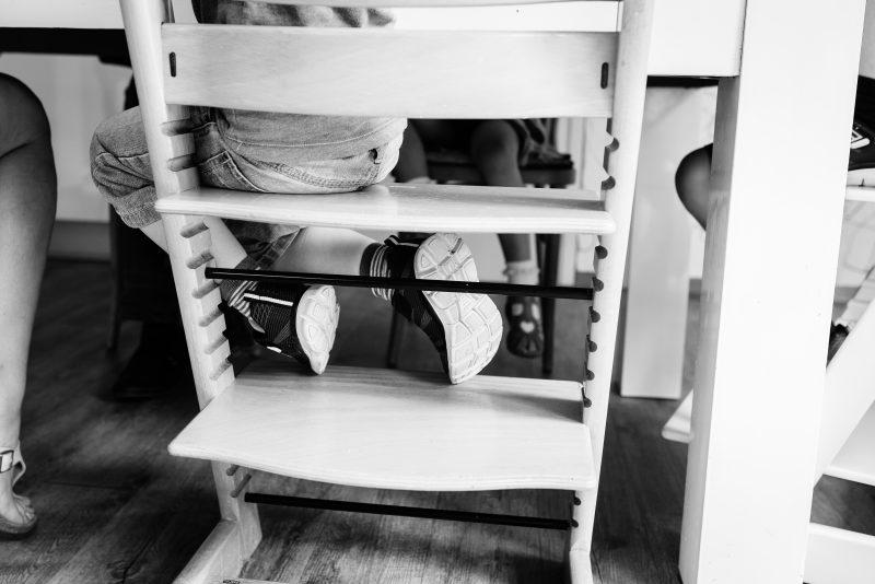 Day in the life bij gezin in Haren, fotograaf Assen, gezin, kindje op stoel, voeten, triptrap stoel, zwart/wit fotografie
