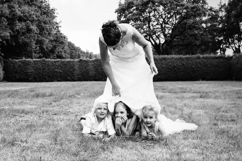 bruidsfotografie Assen, jantina fotografie, natuurlijk licht fotograaf, trouwen, Drenthe, tuinfeest, Trouwen in Hooghalen, kinderen, zomer, verstoppen onder trouwjurk