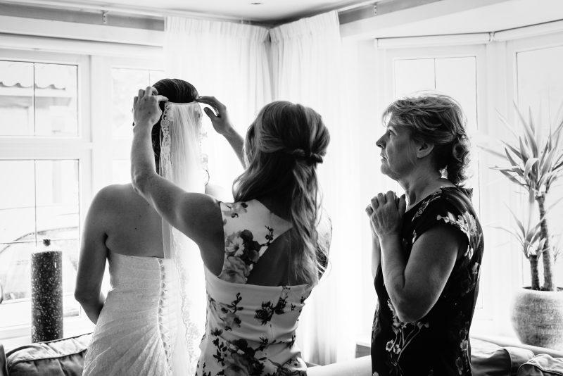 trouwen in Groningen, aankleden van bruid, zwart/wit fotografie, begin dan de trouwdag, familie en vrienden, de laatste puntjes op de 1 zetten met de trouwjurk, moeder en dochter