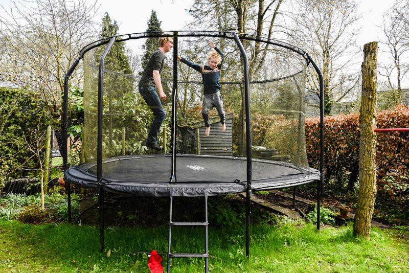 Day in the life, familie reportage, trampoline, jongen met vader springen, fotograaf Assen, natuurlijkliacht fotograaf, fotograaf in Drenthe.