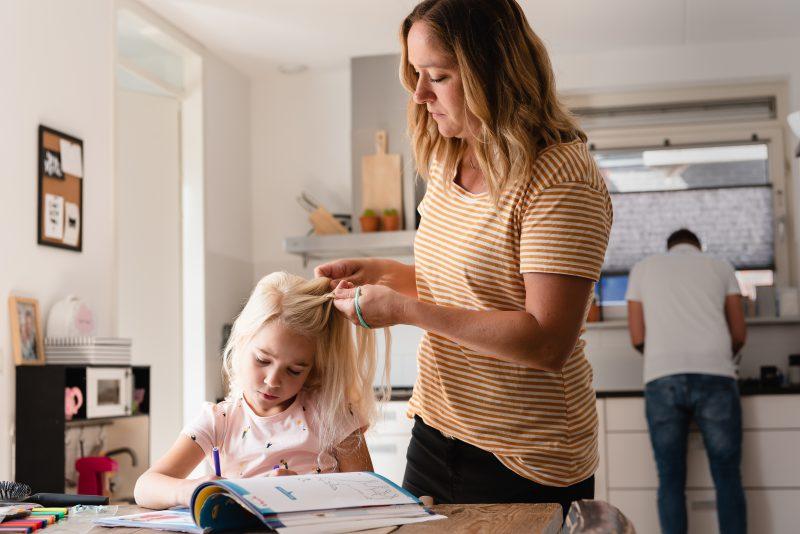 day in the life, familie reportage, bij mensen thuis fotograferen, moeder vlecht het kind haar haar, fotograaf Assen, natuurlijkliacht fotograaf, fotograaf in Drenthe