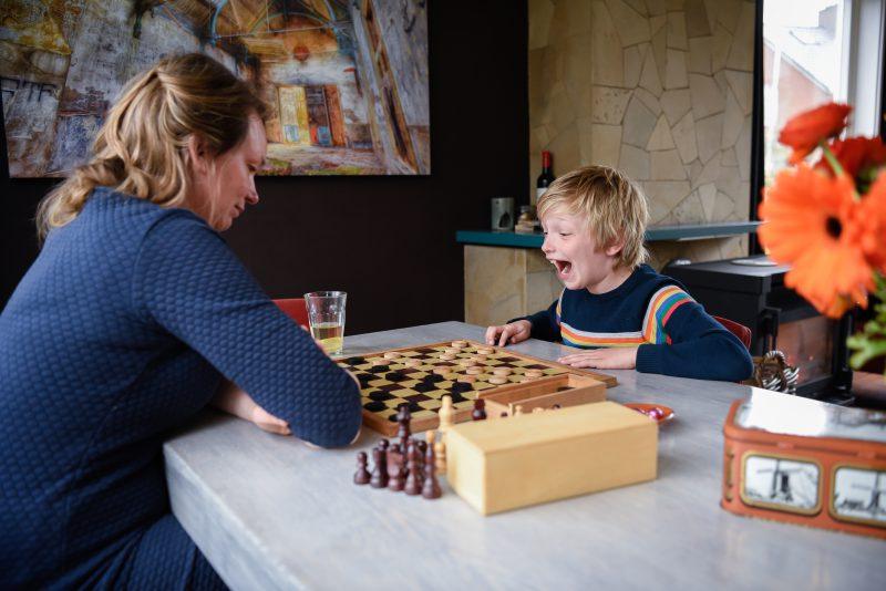 day in the life, familie reportage, bij mensen thuis fotograferen, kind met moeder aan het dammen, fotograaf Assen, natuurlijkliacht fotograaf, fotograaf in Drenthe.